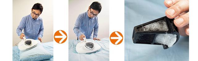 画像: レイコップRNを使って、まくらとふとんを掃除するライター加藤。適度な重量配分と空力設計によって、力を込めることなく、スムーズに生地の上を往復させることができる。まくらとふとんをそれぞれ10回ほど往復させた後、ダストボックスを取り外して見てみると、フィルターに白い粉のようなホコリや繊維が付着していた。