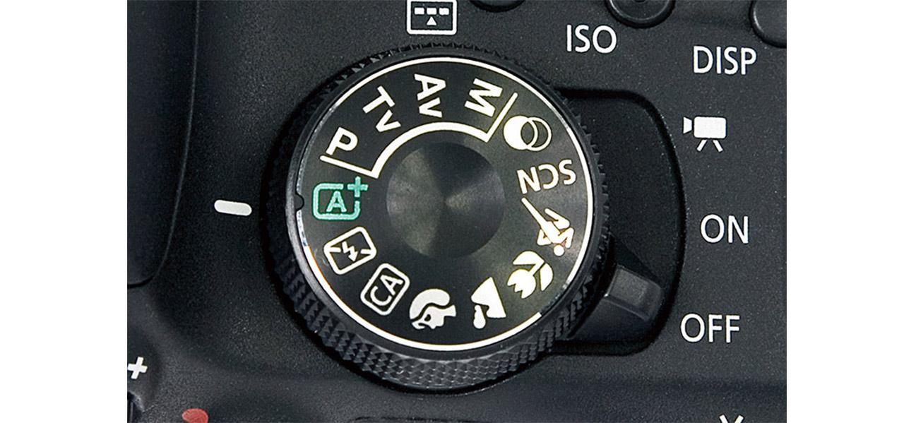 画像: キヤノン・EOS Kiss X9iのモードダイヤル。「M」「Av」「Tv」「P」と書かれているのが、各種撮影モードが並んでいるゾーンとなる。ちなみに「A+」と書かれているのがフルオート。