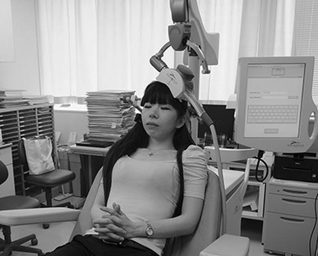 画像: 磁場を発生するコイル装置を頭部に近づけ、らくに座った状態で1回につき40分ほどの刺激を受ける[画像提供/鬼頭伸輔先生(東京慈恵会医科大学)]