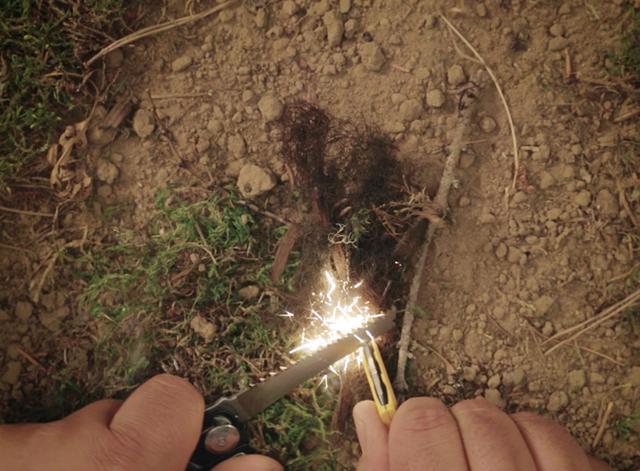 画像: 本体内蔵の合金部を取り出し、ノコギリの背を打ち擦ることで火花を発生させる。