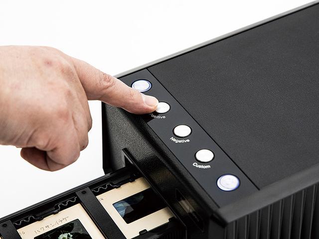 画像: スキャンは、スキャナー本体のボタンを押せば開始される。今回はポジフィルムなので「Positive」ボタンを押すと、ホルダーが自動的にスキャナーの内部へと入っていく。