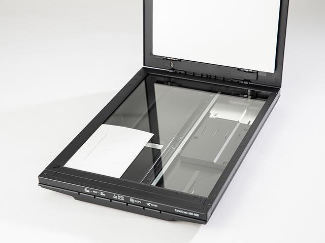 画像: 原稿台の基準位置(本機では左手前)に合わせて、プリント写真を置く。センサーは下側なので写真は裏返しに置くことになる