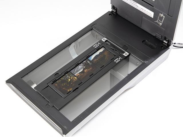 画像: ふたの内側部分にある保護カバーを外し、透過光ユニットを露出させたうえで、原稿台の両端にある溝や突起に合わせ、フィルムホルダーをセットする。