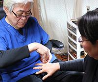 画像: 薬指テープの貼り方を指導する宮本先生