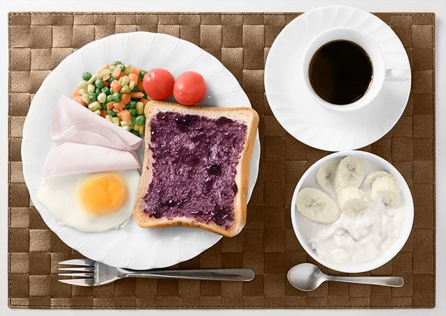 画像: 《一見バランスのよい朝食に見えるが、実はこの1食で糖質は85gを超える》 ◎トースト(6枚切り)▶糖質:28g ◎ブルーベリージャム(20g)▶糖質:7.9g ◎ミニトマト(2個:35g)▶糖質:2g ◎ミックスベジタブル(60g)▶糖質:6.3g ◎ハム(20g)▶糖質:1.4g ◎卵(1個)▶糖質:0.2g ◎バナナ(1/2本)▶糖質:10.5g ◎ヨーグルト(150g)▶糖質:7.3g ◎ハチミツ(20g)▶糖質:16g ◎コーヒー(160ml、砂糖5g入り)▶糖質:6.1g