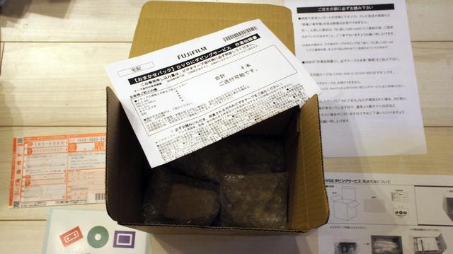 画像: テープを1本ずつ緩衝材で包み、ダンボール箱に入れる。作業確認書も一緒に入れて箱を閉める。