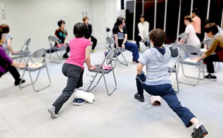 画像: 中央で足を延ばすストレッチを教える大村先生