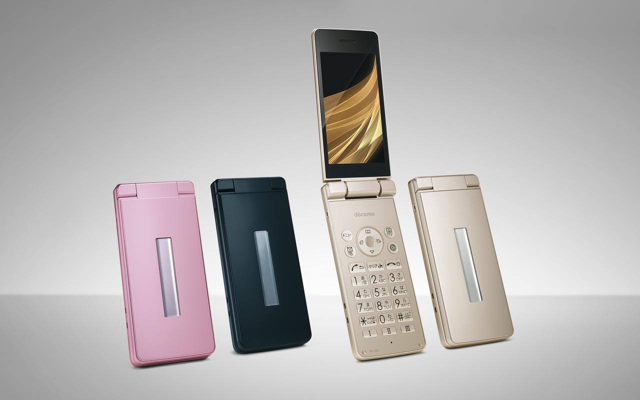 画像: ボディの中央に通知用のサブディスプレイを装備している。ベース色はゴールド、ブラック、ピンクの三色展開で、どの色にも三色のリアカバーが付属する。横置きの充電台も付属する。 www.nttdocomo.co.jp
