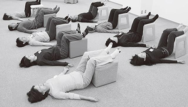 画像: 写真はエゴスキュー体操の「足乗せゴロ寝」。どんな症状の人でもやっていただきたい基本のエクササイズ。寝ているだけの体操だが、関節が正しい位置へと導かれる