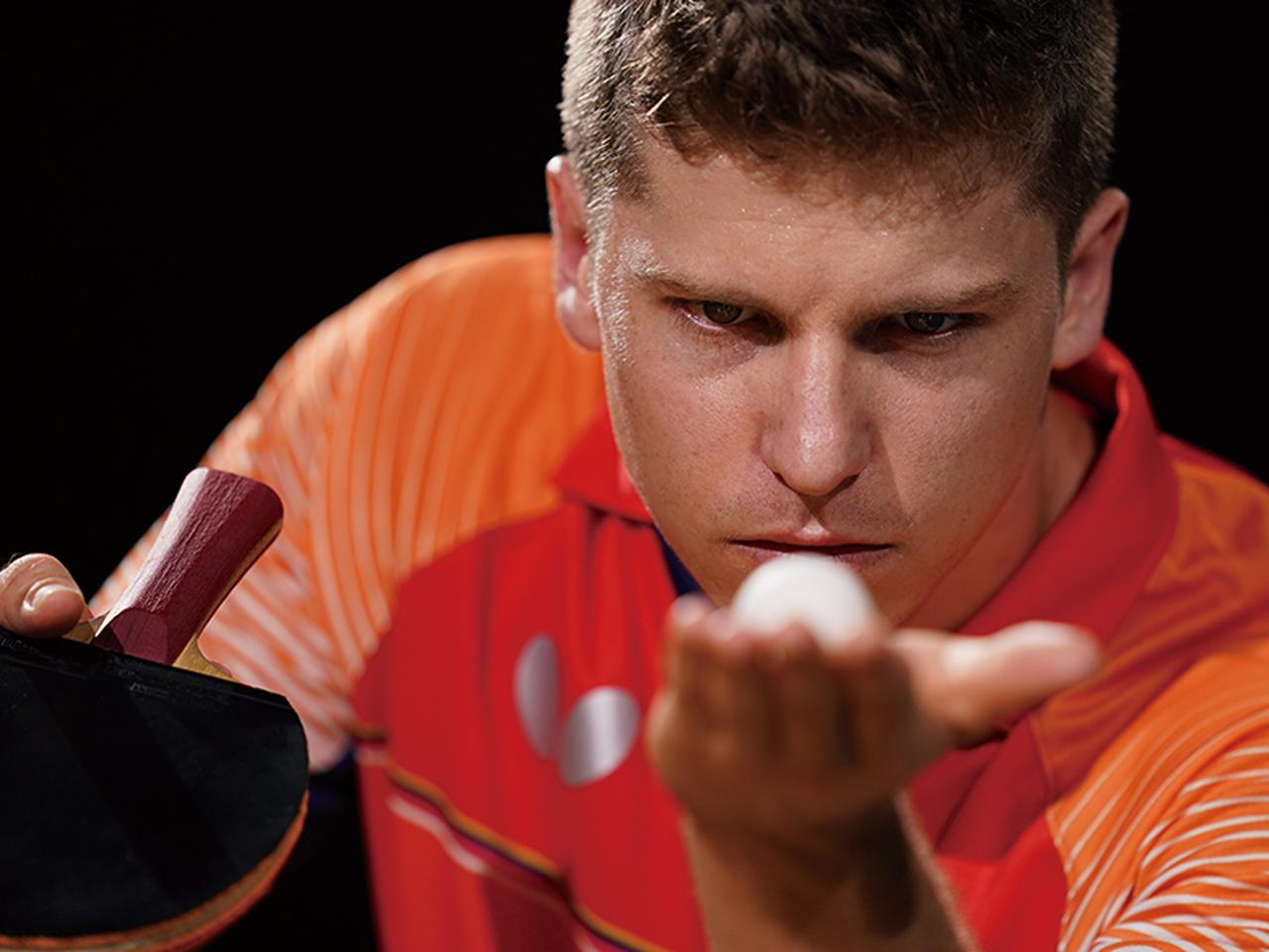 画像: 卓球選手の集中した一瞬の表情にピタリとフォーカス。手前にある手のひらと球はきれいにボケている。
