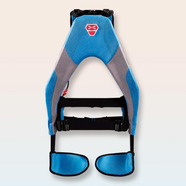 画像: ポンプで空気を入れて作動 クッションのように見えるのが人工筋肉。肩と腹部をハーネスで固定し、腿の前側にパッドが当たる構造。ポンプで空気を入れる。