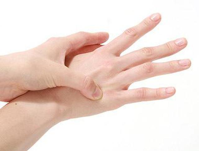 画像: 手の甲の薬指と小指の間を触り、最も痛いところを押す。