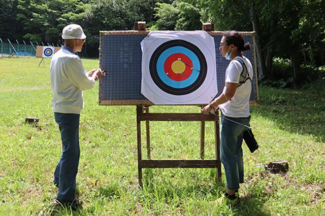 画像: 打ち終わった的の前で指導を受ける筆者、腕というよりは弓の性能のおかげで思った以上に的には当たります。(写真撮影:佐々木富士子)