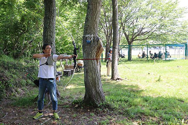 画像: はじめての本物の弓と矢に緊張気味の筆者、それでも的に矢が当たると非常に楽しいです。個人的には非常にハマりそうな予感がします。(写真撮影:佐々木富士子)