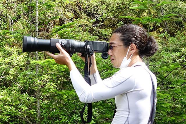 画像: カメラを構える筆者です。超望遠なので、ほとんどのシーンでは三脚を使用しましたが、シャッター速度によっては手持ちでも撮影可能でした。(写真撮影:西川藍)