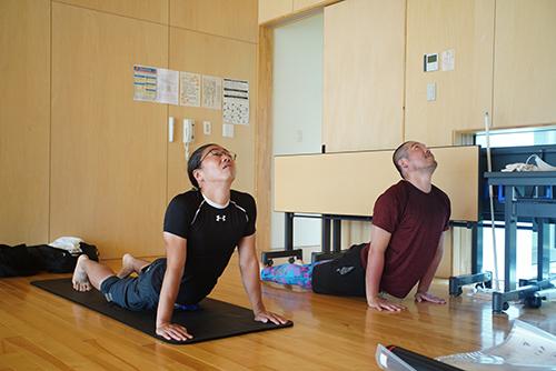画像: 斉藤先生の指導の下、初体験のアシュタンガヨガを行う筆者です。各関節の伸ばし方や向きなどが先生と違っているのが写真だとよくわかります。(写真撮影:松岡美雪)