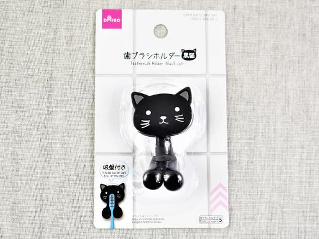 画像: キュートな黒猫が歯ブラシをホールド