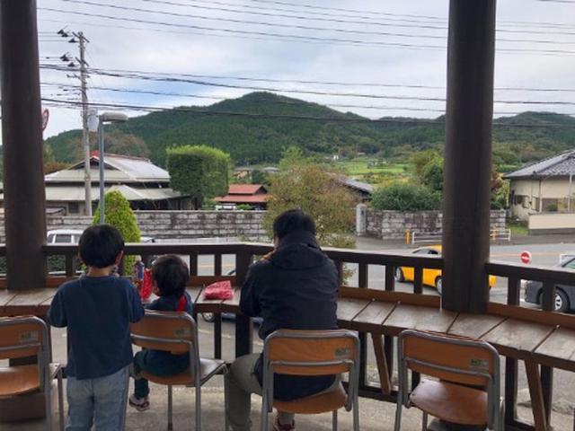 画像: 山と目の前を行き交う車を眺めながらパンを食べる