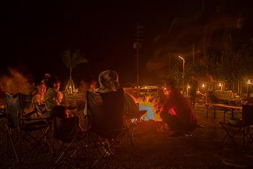 画像: 日が暮れると毎日行われるキャンプファイアー。揺れる火のまわりでゆっくり時間が流れます。隣で子どもたちが花火を楽しんでいました。
