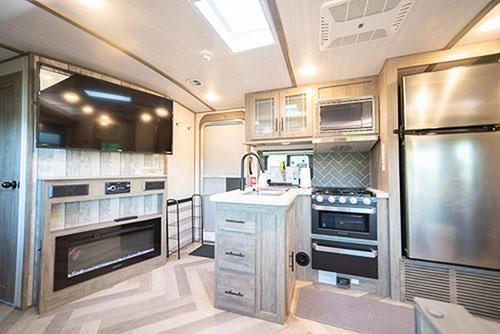 画像: リビングのソファからキッチン側をみたところ。大型テレビに家庭用クラスの冷蔵庫、電子レンジに三ツ口コンロ、オーブンまでが完備されています。