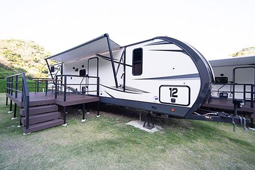 画像: バーベキューデッキ付きのキャンピングトレーラー。大きさは高さが約3.5m、全長は約11mです。これが1室扱いになります。