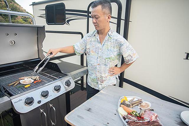 画像: アメリカ映画しかみたことのないようなバーベキューコンロで肉を焼く様子です。明るいうちから沖縄といえば定番のオリオンビールを飲んでいます。