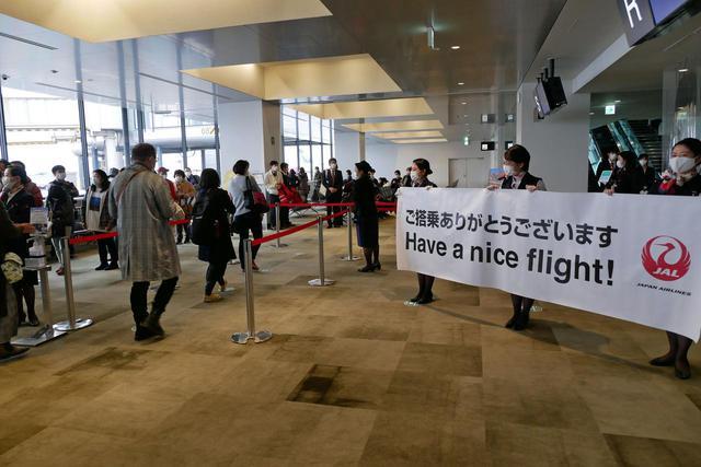 画像: JALのスタッフに見送られて国内線Sゲートで搭乗手続きをする旅客の方々