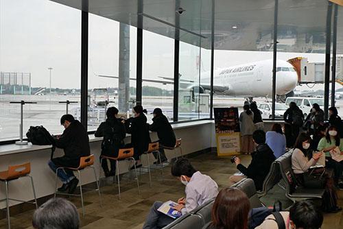 画像: 搭乗ゲート付近で期待を見ながらフライトを待つ旅客の方々