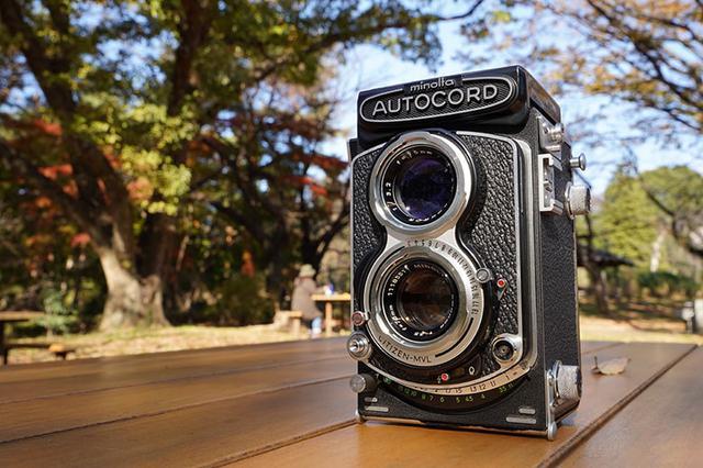 画像: 撮影に使用するカメラをテーブルの位置まで下げて、水平に近いアングルで被写体のカメラを狙う。この際、被写体のレンズの向きを意識して、画面左側を広く空けて背景を写し込む。このカメラ位置(によるアングル)と構図によって、その場の様子や雰囲気が伝わってくる写真になった。 ソニー α7 III Vario-Tessar T* FE24-70mm F4 ZA OSS(35mmで撮影) 絞り優先オート F16 1/40秒 WB:曇天 ISO250
