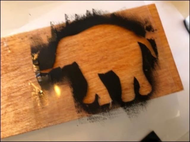画像: セロハンテープを使ってステンシルシートを木材に貼り付ける。