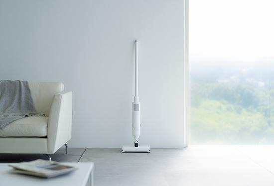 画像: 付属する充電スタンドも極力シンプルに仕上がっている。掃除機を使っていないときには、室内のインテリアと違和感なく調和するデザインを追求。後ろにやや傾斜した角度で、美しく自立して設置できるようになっている。
