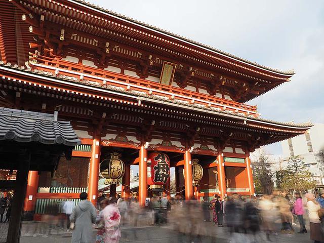 """画像: まだ十分に明るい夕方、寺院前の大きな門にカメラを向ける。その門の周囲には多くの参拝客や観光客が行き来している。その人の動きをライブND機能を使用して、2秒の低速シャッターで撮影(ND32に設定)。大きくブレた群衆により、独特な""""賑わい""""が表現できた。なお、使用カメラには強力な手ブレ補正機能が搭載されているが、細心の注意を払いながらシャッターを切った。 オリンパス OM-D E-M1X M.ZUIKO DIGITAL ED 12-100mm F4.0 IS PRO(12mmで撮影) シャッター優先オート F11 2秒 ライブND使用 WB:オート ISO200"""