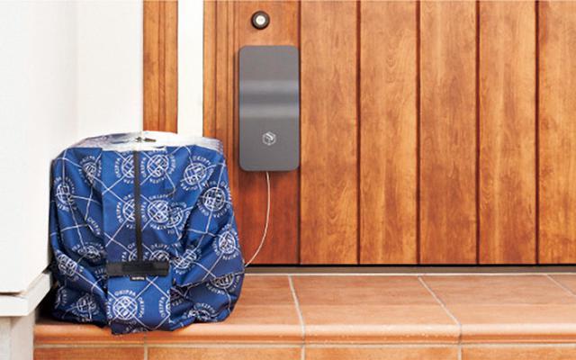 画像: 置き配バッグ「OKIPPA」を収納しておく専用ケース「ATOMO」を玄関ドアに取り付ける。OKIPPAは、2リットルのペットボトルが18本も入るかなり大きなサイズだが、配達員が取り出すまでは玄関先のスペースを占有することがない。