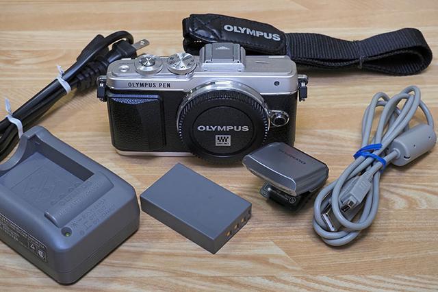 画像: オリンパス PEN Lite E-PL7と、その付属品一式。比較的新しいカメラだと、専用バッテリーを本体内で充電するタイプもあるが、PEN Lite E-PL7では充電器が不可欠(AC電源コードは他製品のモノが流用できそうだが)。