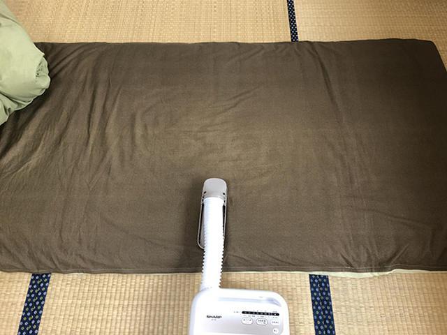 画像: ホースを伸ばし、布団の横端から1/3の位置にアタッチメントを設置する。