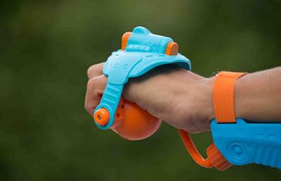画像: タンクは腕部分で、手に持つ発射機構とはホースで連結されている。手の平側のゴム球を握ると水流発射。ピンクモデルもある。