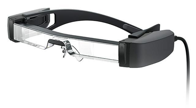 画像: 眼鏡のようにかけると、透明な部分に入力した映像が表示され、実際の風景に重ね合わせたシースルー映像を見ることができる。音は、イヤホンを接続して楽しめる。