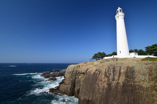 """画像: ピクチャースタイル(仕上がり設定)を「風景」に設定し、C-PLフィルターも使用する。それによって、青空と海の""""青色""""に鮮やかさと深みが増す。白亜の灯台の白さも際立つ。また、海面の反射が除去された事で、岩場の白い波もより目立つようになった。 ニコン D5300 AF-P DX NIKKOR 10-20mm f/4.5-5.6G VR(10mmで撮影) 絞り優先オート F11 1/60秒 +0.7補正 WB:オート ISO100 C-PLフィルター使用"""