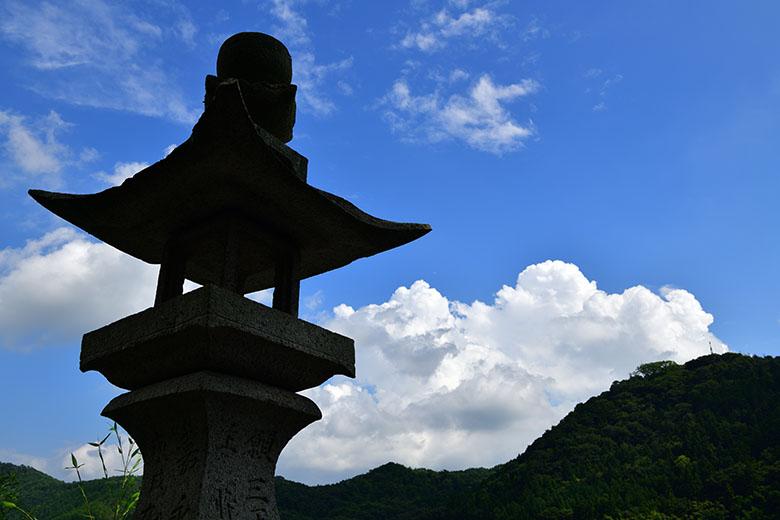 画像: 山にある神社を目指して、長い石段を上って行く。途中、遠方の山から入道雲が湧き立つのが見えた。その夏らしい光景を、石段脇の石灯籠を絡めて撮影。ただし、時間帯のせいか、空気の透明度のせいか、仕上がり設定で「風景」を選択しても、ややメリハリに欠ける印象(C-PLフィルターは持参していなかった)。そこで、選択した「風景」をさらに調整。明瞭度を上げてメリハリをつけ、彩度も上げて色のインパクトも強めた。 ニコン D850 AF-S NIKKOR 24-70mm f/2.8E ED VR(31mmで撮影) 絞り優先オート F11 1/200秒 +0.3補正 WB:晴天 ISO64