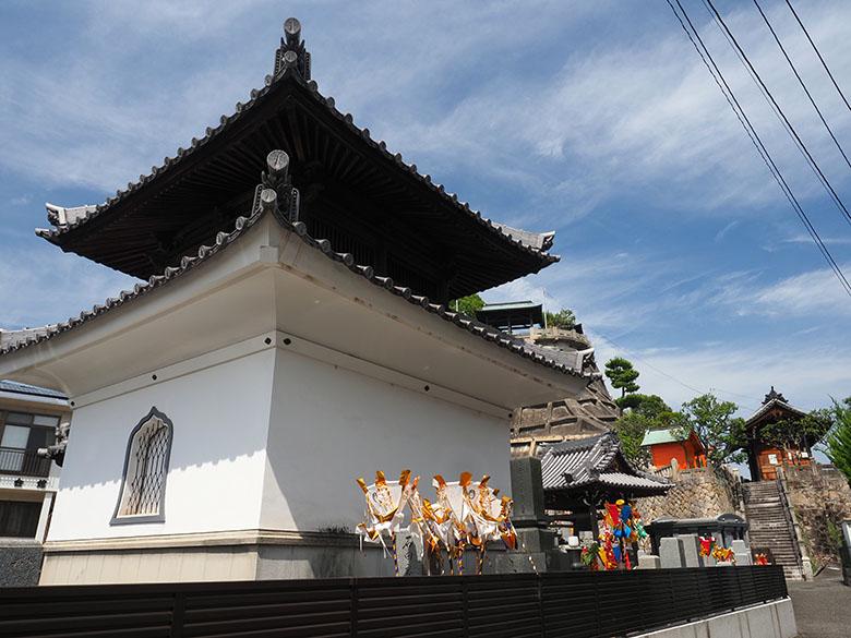 画像: 夏の帰省時に、広島市内を散策。画面右下に写っている狭い路地の先には、目的地である高台の神社が見える。また、路地の入口にある寺院には、白色や色鮮やかな盆灯籠が立てられている。この地方(広島県西部)などで見られる風習である。画面内にこの盆灯籠を入れた事で、お盆の風情と同時に地域性も出せた。 オリンパス OM-D E-M1 MarkII M.ZUIKO DIGITAL ED 12-40mm F2.8 PRO(12mmで撮影) 絞り優先オート F11 1/80秒 -0.3補正 WB:オート ISO200 C-PLフィルター使用