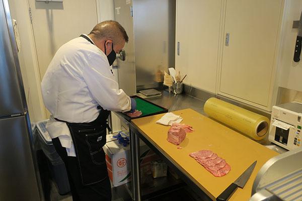画像: 現場主義の澤氏はキッチンで自ら肉をカットし、食事する顧客に気軽に接する。