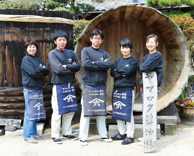 """画像: みんなで""""職人ポーズ"""" ヤマロク醤油のスタッフと山本さん。カメラを向けると、「ぼくたち、きまりのポーズがあるんです」と、いっせいに"""