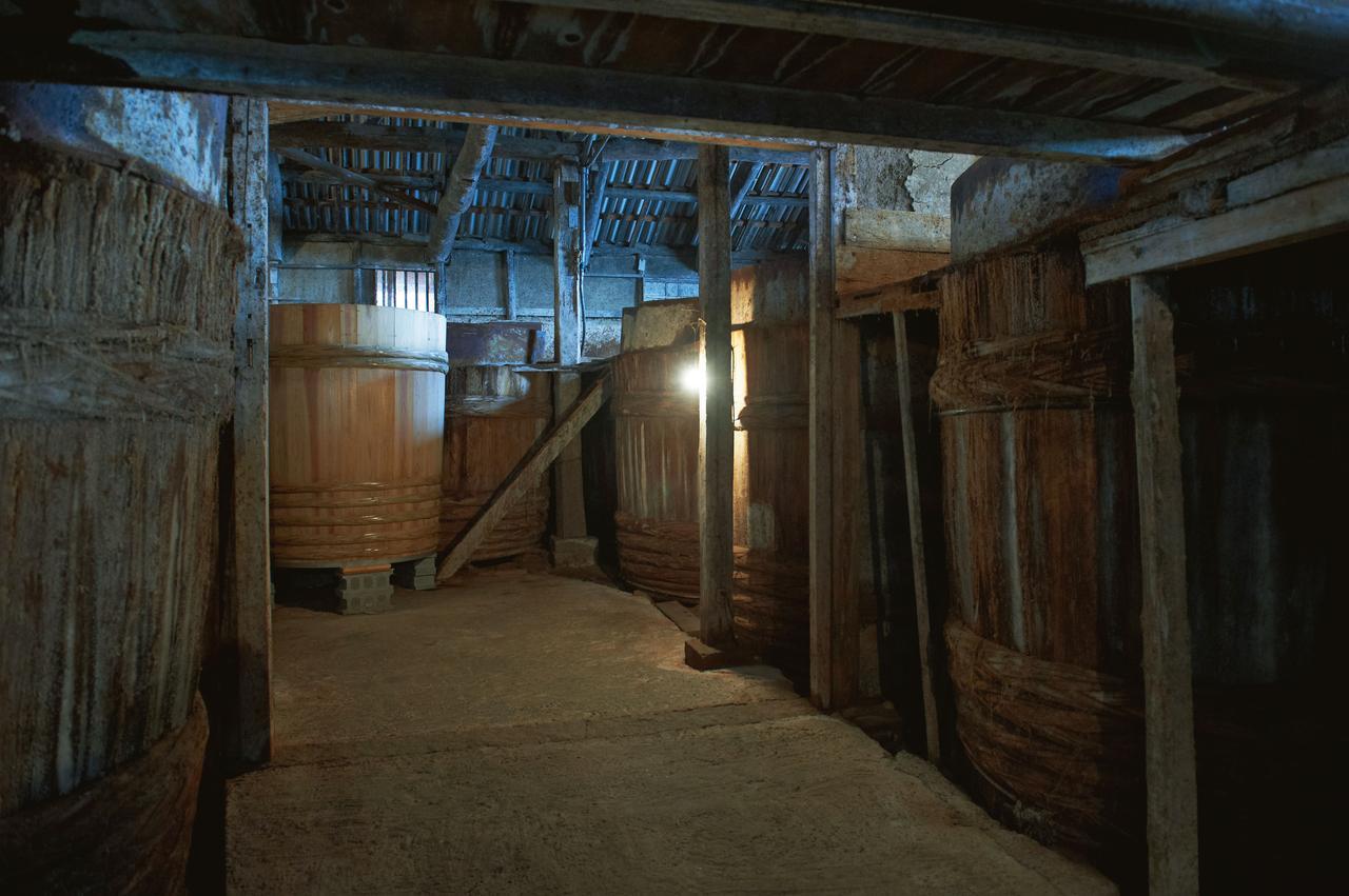 画像: 醤油蔵には、現在、61本の桶が納められている。土間や梁や木桶に、多様な微生物が何百年にもわたって暮らしている