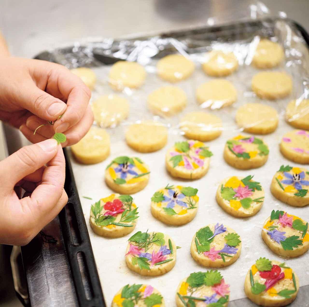 画像: 色とりどりのハーブの花をあしらったクッキーは、まるふく農園や日曜市でも販売している。「お花は10種類くらいを使って、見た目重視で飾ります。ざらめを使った、ザクザクの食感もポイントです。かわいいからギフトにもいいと思います」