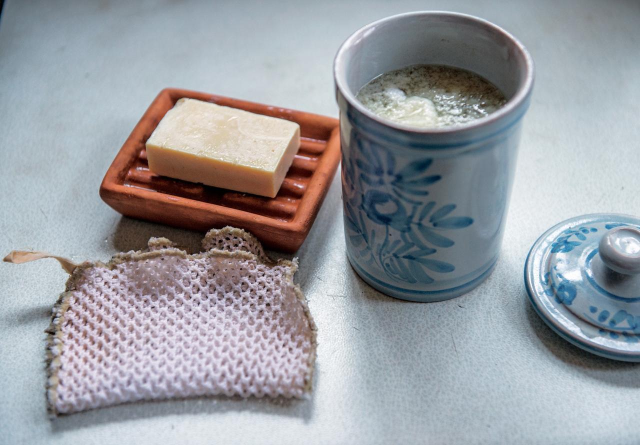 画像: 右の液状廃油石けんを溶かし、ふきんをつけ置き洗い。食器は固形石けんを左下の漁網に付けて洗う。地元の福祉施設でつくられたものを愛用