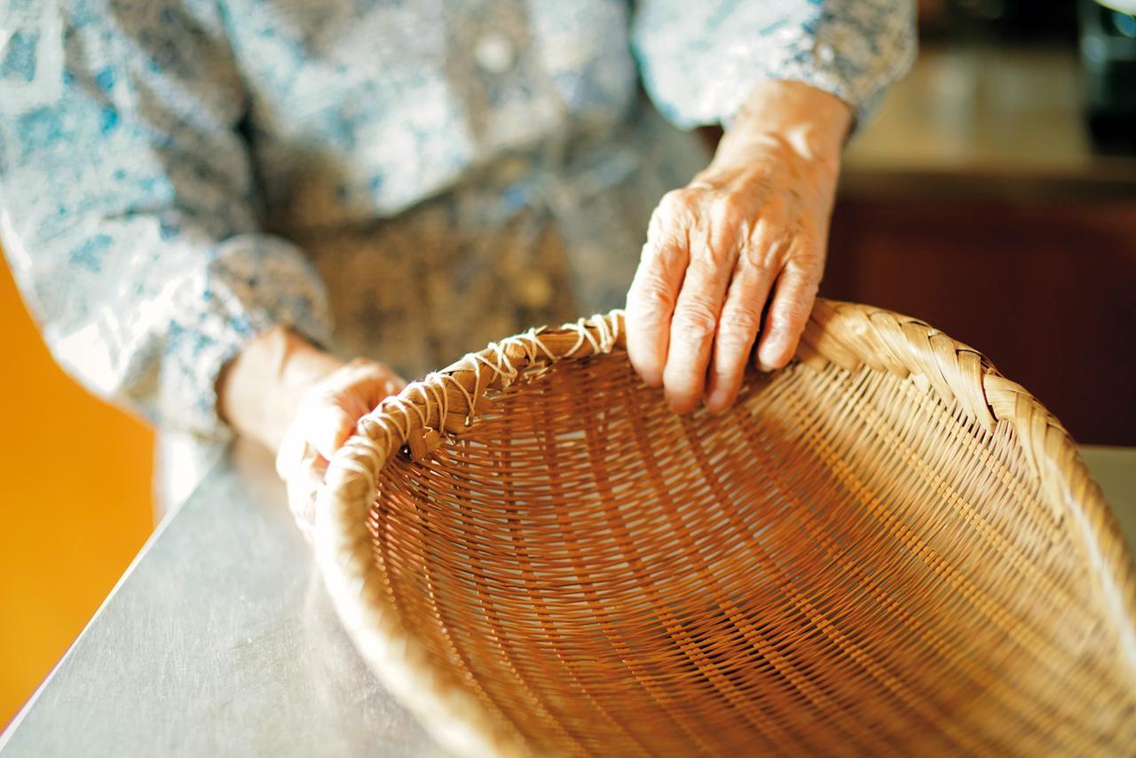 画像: 大きな竹ざるの縁の部分を、ひもを使って修理し、使いつづけている