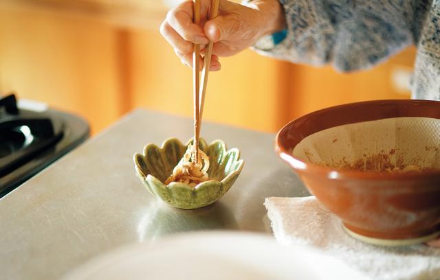 画像: 玉ねぎを、ごまとしょうゆであえ、盛りつける。玉ねぎは自然農法のもの、しょうゆは伝統製法でつくられたものを使う