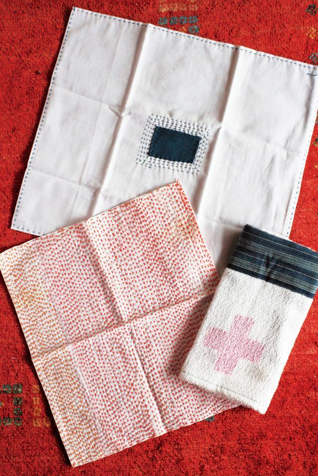 画像: ノベルティのタオルなどは藍色のはぎれで社名を隠して使う。手前の刺し子のふきんはさらしを使いやすい大きさに裁断し、縫ったもの