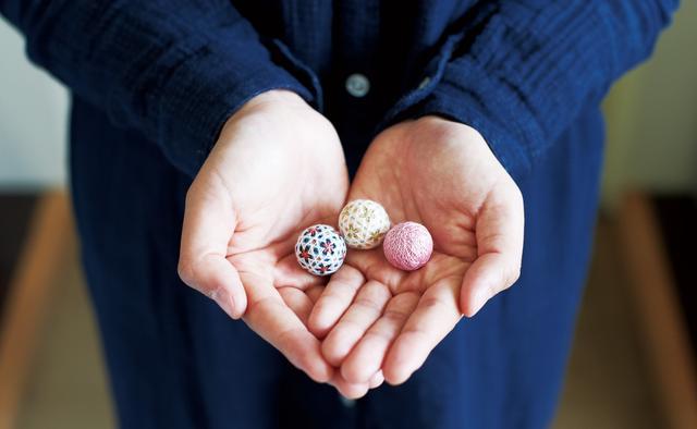 画像: 飴玉のように小さな手まりは、永子さんがつくりはじめた。木綿糸を1本取りにして、小さくても模様をくっきりと、繊細に