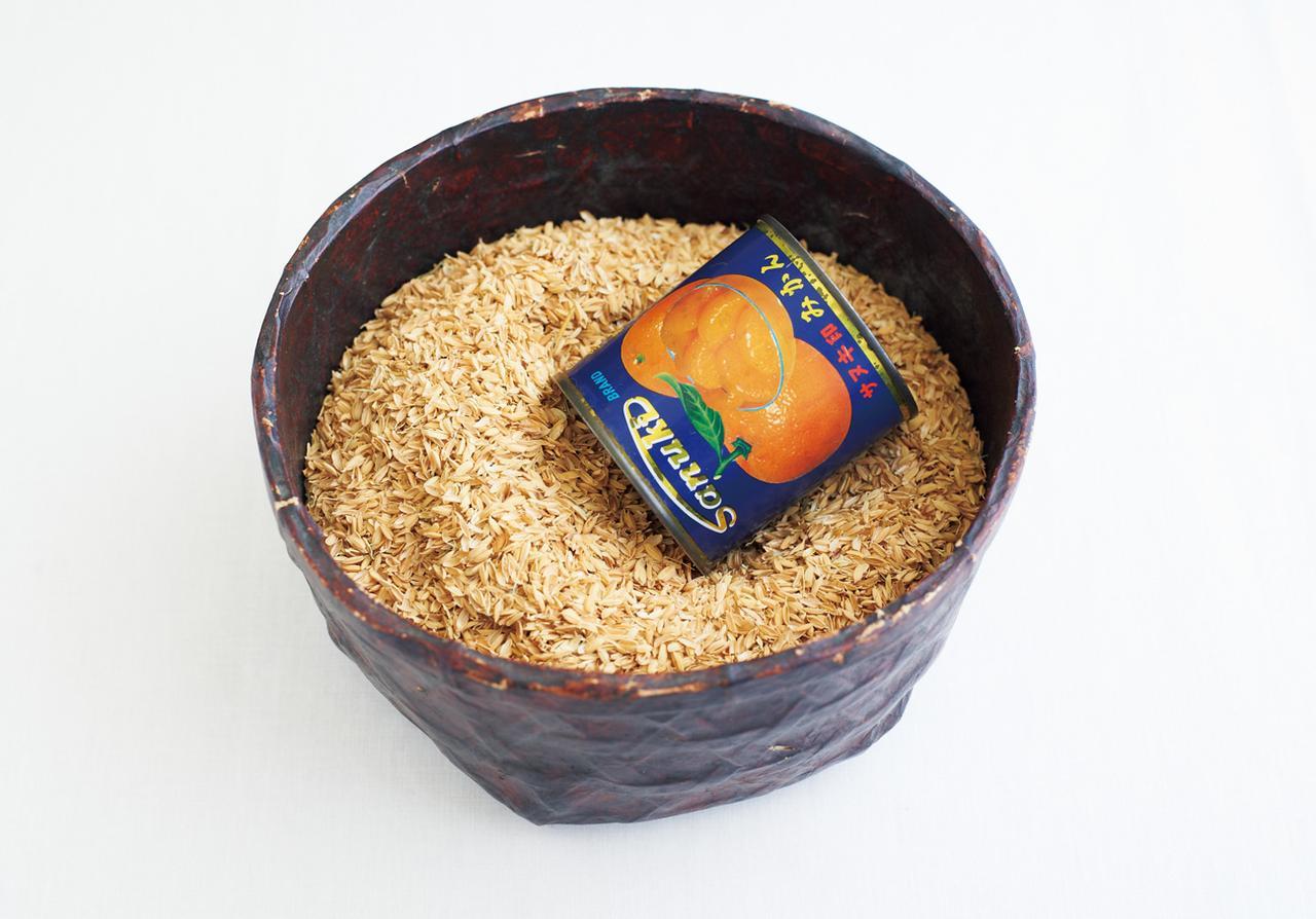 画像: 籾殻を薄紙にくるみ、手まりの芯にする。義父母の代から使っている果物缶1カップで標準サイズの手まりがひとつできる